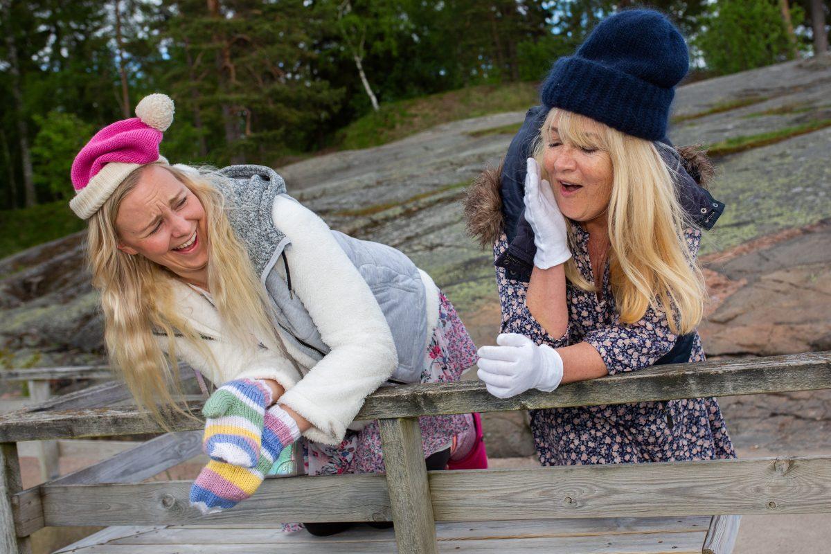 Elina Aalto ja Jaana Saarinen nauravat nojatesssaan aitaan.